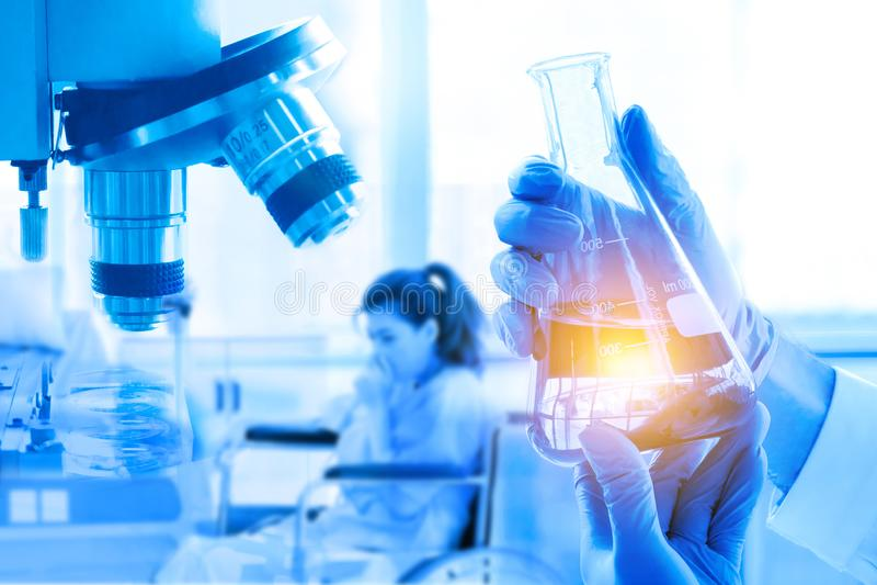 Doppia esposizione, boccetta della tenuta della mano, microscopio, nella ricerca medica al laboratorio immagini stock libere da diritti