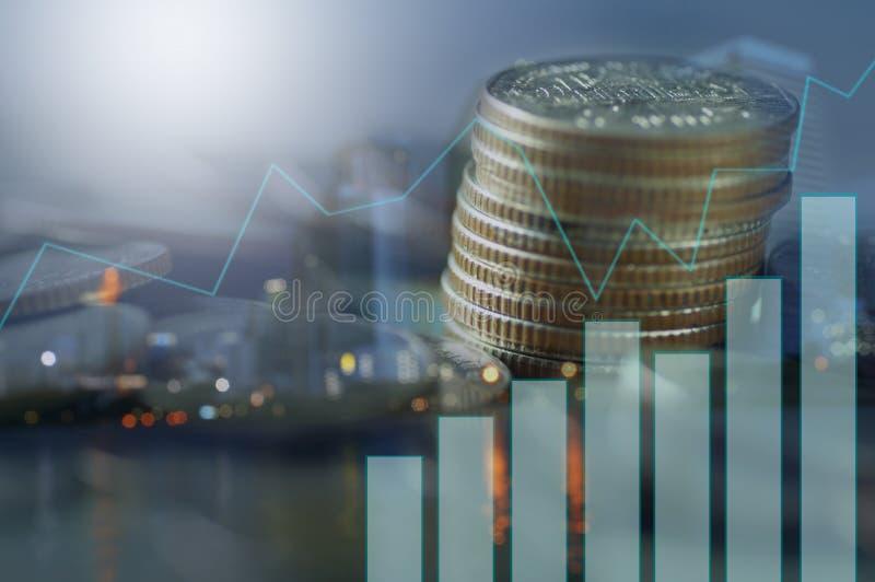 Doppia esposizione dell'impilato di delle monete con la città di notte e del grafico, concetto come finanza fotografia stock