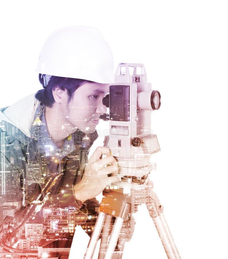 Doppia esposizione dell'ingegnere che lavora con il theodo dell'attrezzatura di indagine fotografie stock libere da diritti