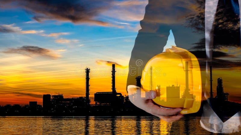 Doppia esposizione dell'ingegnere con il casco giallo di sicurezza per sicurezza dei lavoratori e la pianta in bianco e nero di i fotografia stock