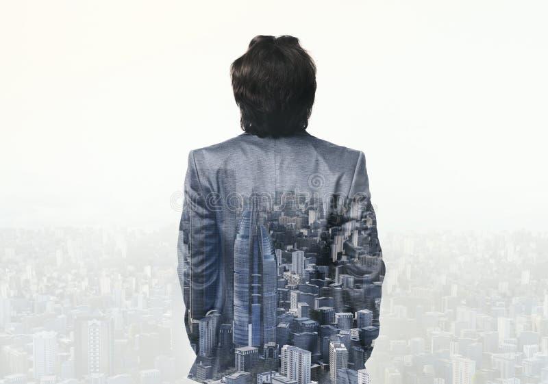 Doppia esposizione dell'uomo d'affari che cammina sul fondo astratto della città immagini stock
