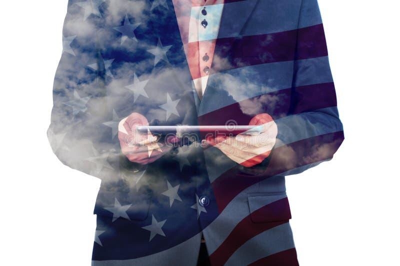 Doppia esposizione dell'uomo d'affari con la nuvola e la bandiera dell'America immagine stock