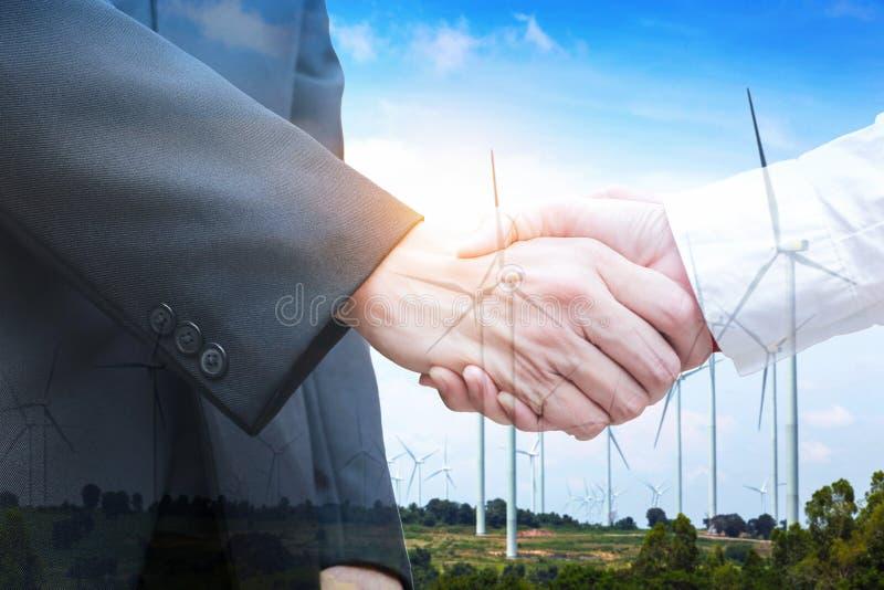 Doppia esposizione della stretta di mano con il generatore eolico Concetto di ecologia fotografie stock