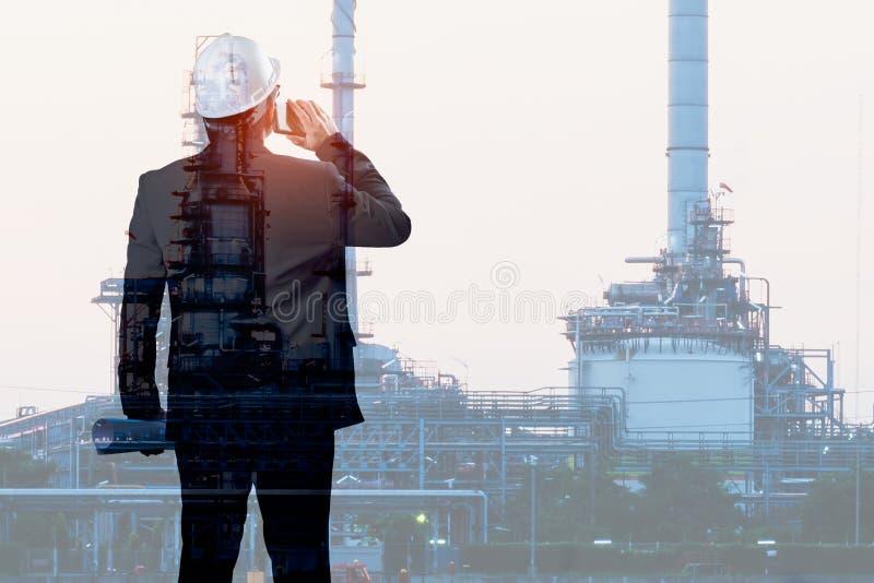 Doppia esposizione dello smartphone di conversazione dell'ingegnere con la raffineria di petrolio fotografia stock libera da diritti