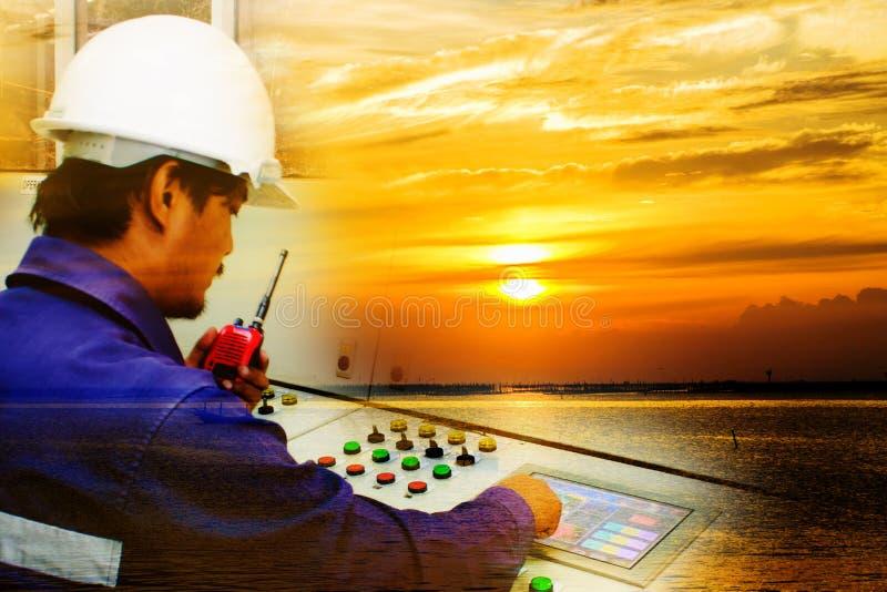 Doppia esposizione di funzionamento dell'ingegnere e di bello cielo arancio fotografie stock
