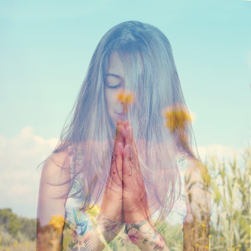 Doppia esposizione di una giovane donna che medita e terre pacifiche fotografia stock libera da diritti