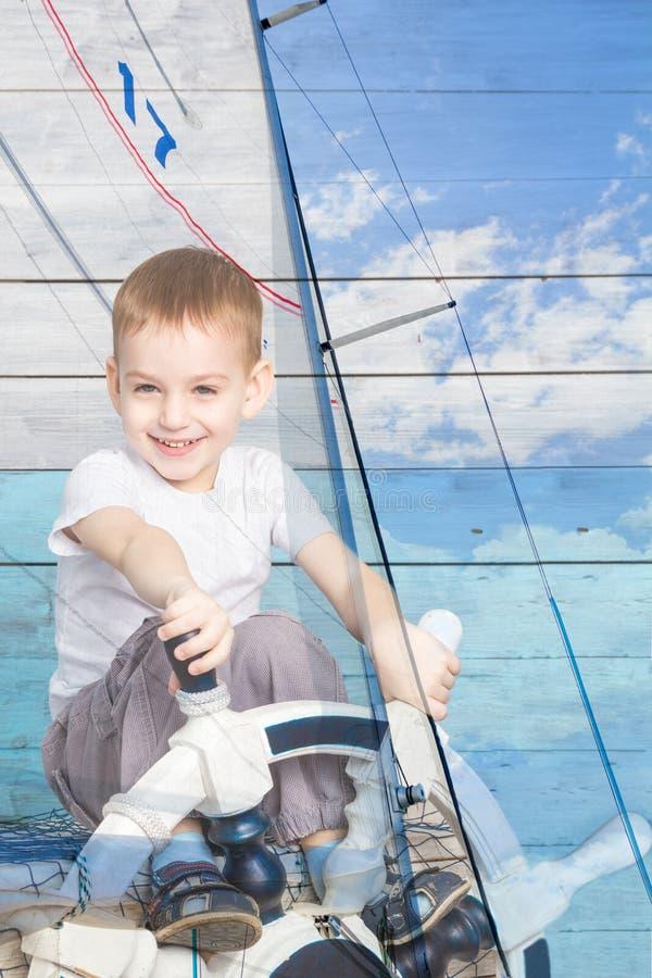 Doppia esposizione un ragazzino al timone ed all'yacht immagini stock libere da diritti