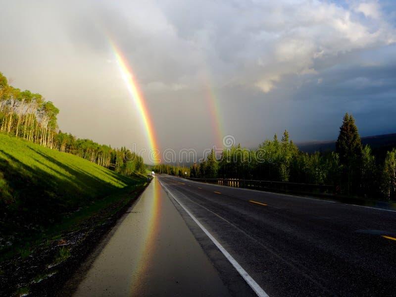 Doppio arcobaleno che guida in montagne sulla strada fotografia stock libera da diritti