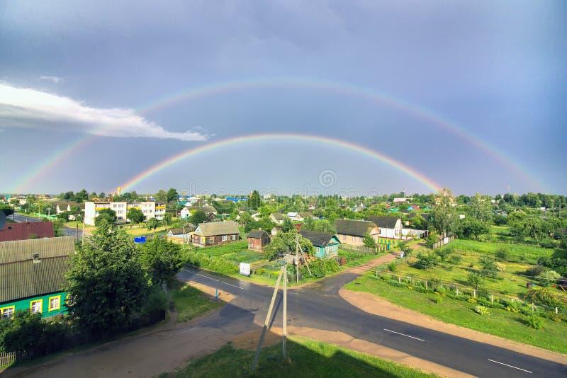 Doppio arcobaleno sopra la città fotografia stock