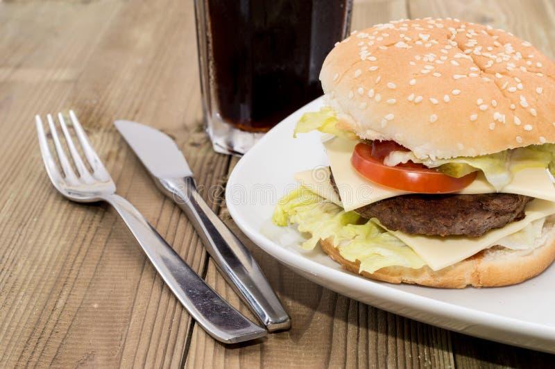 Doppio cheeseburger con la bibita analcolica fotografie stock