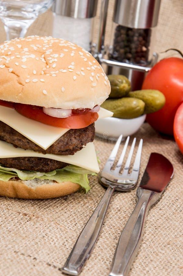 Doppio hamburger con gli ingredienti e la coltelleria fotografia stock