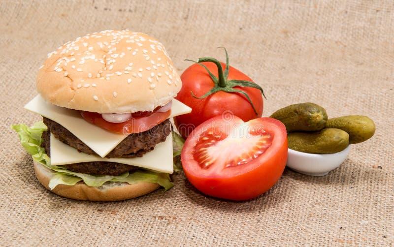 Doppio hamburger su fondo rustico immagini stock libere da diritti