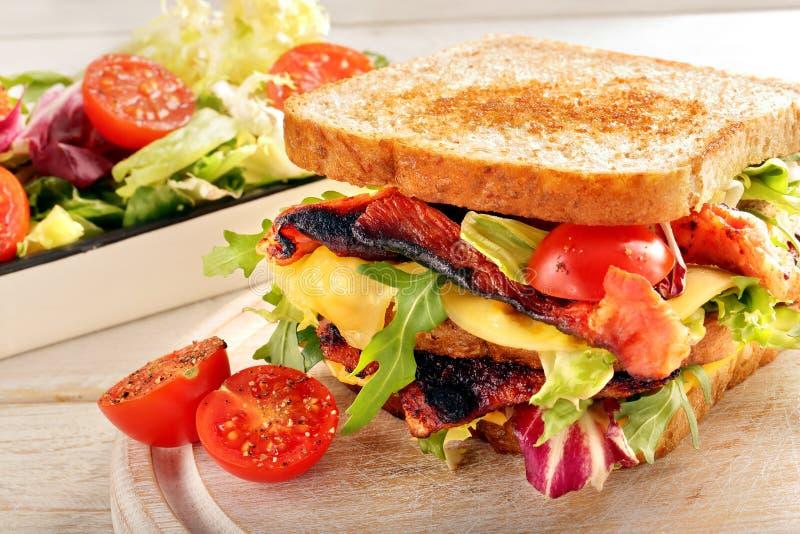 Doppio panino con il formaggio e le verdure del bacon su backg di legno fotografia stock
