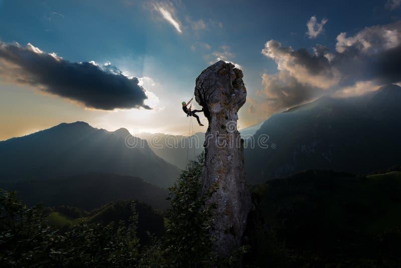 Doppio rappelling della corda di uno scalatore dalla punta di una roccia in a fotografie stock libere da diritti