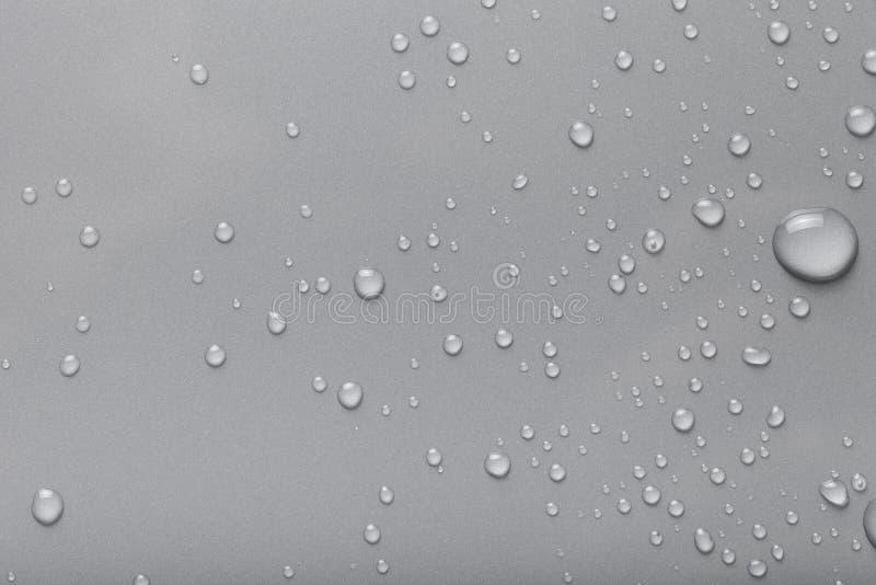 Dops av vatten på en färgbakgrund grått royaltyfri bild