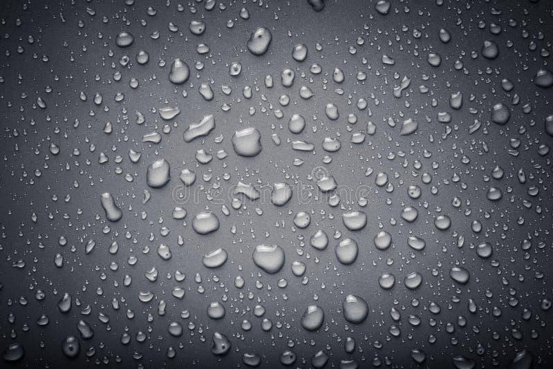 Dops av vatten på en färgbakgrund grått tonat arkivbilder