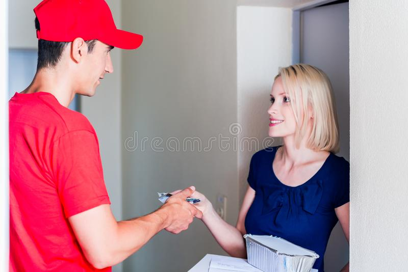Doręczeniowy mężczyzna bierze zapłatę od żeńskiego klienta obrazy stock