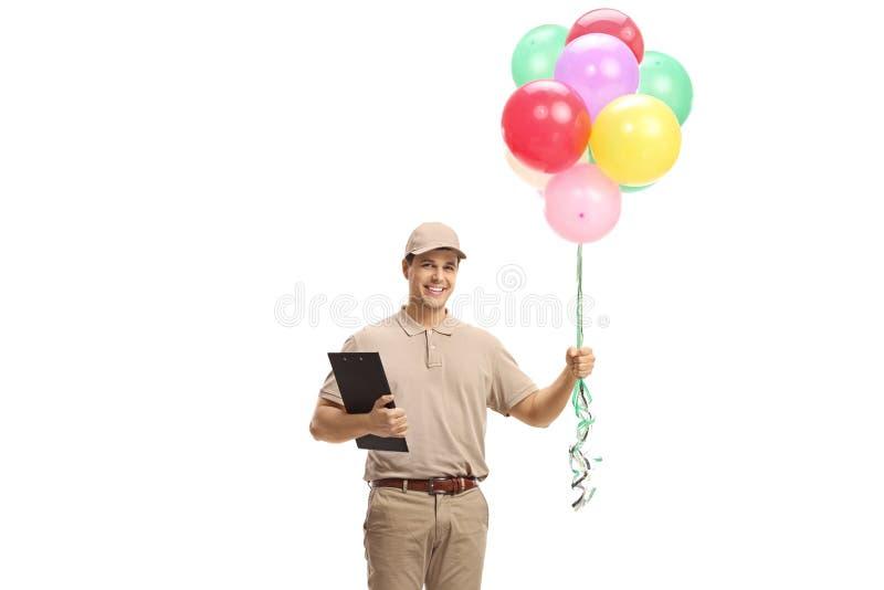 Doręczeniowy mężczyzna niesie wiązkę balony obraz royalty free
