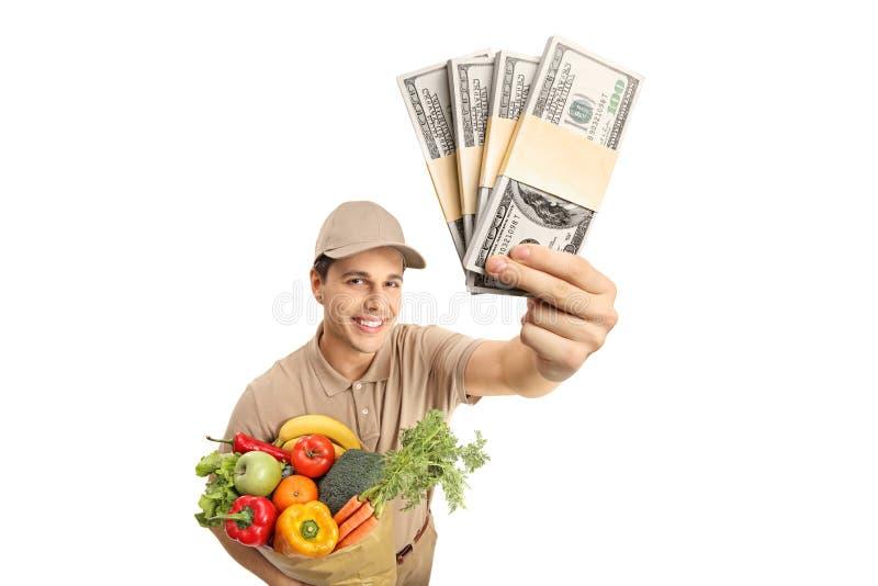 Doręczeniowy mężczyzna trzyma torbę sklepy spożywczy i pliki pieniądze obraz stock