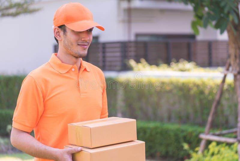 Doręczeniowy mężczyzna w pomarańczowym dowiezieniu w pakunku zdjęcia stock