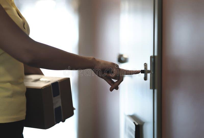 Doręczeniowy osoby dzwonienia doorbell podczas gdy dostarczający pakunek stwarzać ognisko domowe drzwi zdjęcia stock