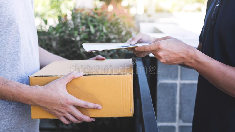 Doręczeniowy poczta mężczyzna daje pakuneczka pudełku odbiorca i podpis forma, Młody właściciela podpisywania kwit dostawa pakune fotografia stock