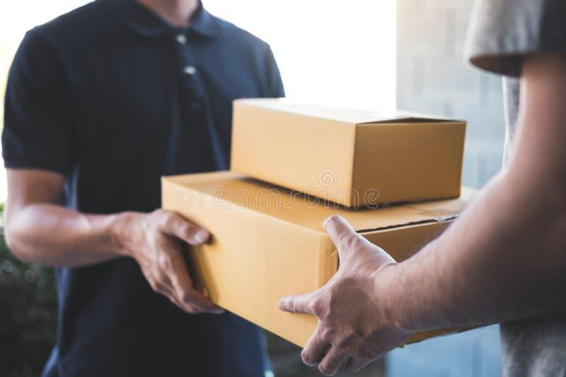 Doręczeniowy poczta mężczyzna daje pakuneczka pudełku odbiorca, Młody właściciela akceptować kartonu pakunek od poczta transportu obraz royalty free
