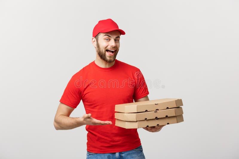 Doręczeniowy pojęcie: Młodzi caucasian Przystojni pizza doręczeniowego mężczyzna mienia pizzy pudełka odizolowywający nad popiela zdjęcia stock