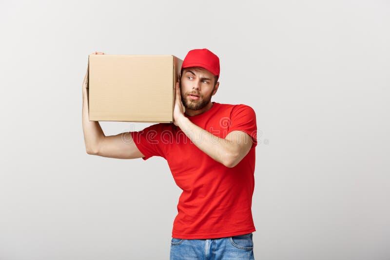 Doręczeniowy pojęcie - portret Ciekawy caucasian przystojny doręczeniowy mężczyzna słucha inside pudełkowaty pakunek Odizolowywaj zdjęcia royalty free
