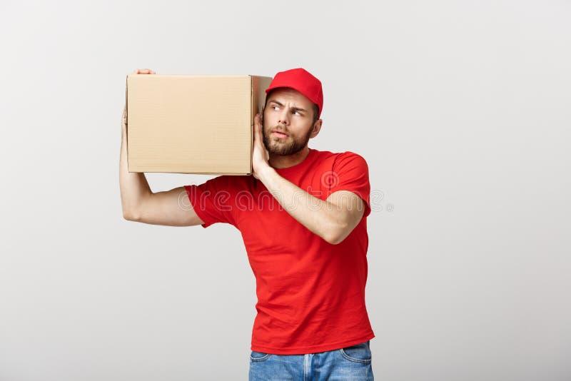 Doręczeniowy pojęcie - portret Ciekawy caucasian przystojny doręczeniowy mężczyzna słucha inside pudełkowaty pakunek Odizolowywaj fotografia stock