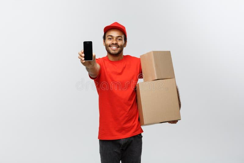 Doręczeniowy pojęcie - portret Przystojnego amerykanina afrykańskiego pochodzenia doręczeniowy mężczyzna lub kurier z pudełkowaty obrazy stock