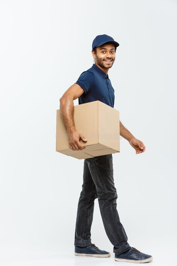 Doręczeniowy pojęcie - portret Szczęśliwego amerykanina afrykańskiego pochodzenia doręczeniowy mężczyzna w błękitnym sukiennym od zdjęcie stock