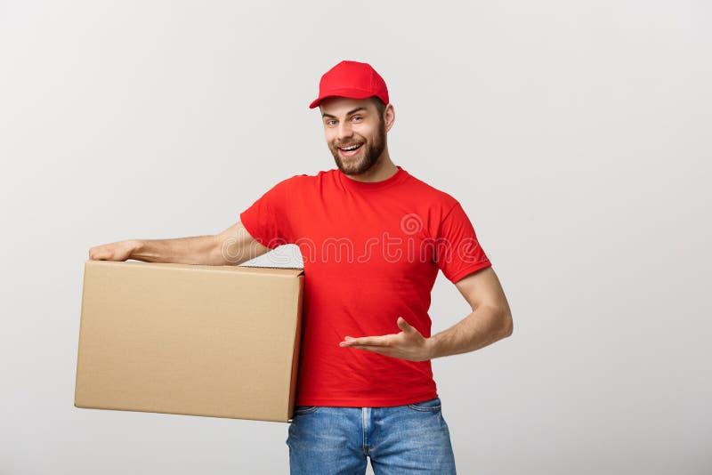 Doręczeniowy pojęcie - portret Szczęśliwy Kaukaski doręczeniowy mężczyzna wskazuje rękę przedstawiać pudełkowatego pakunek Odizol obraz stock