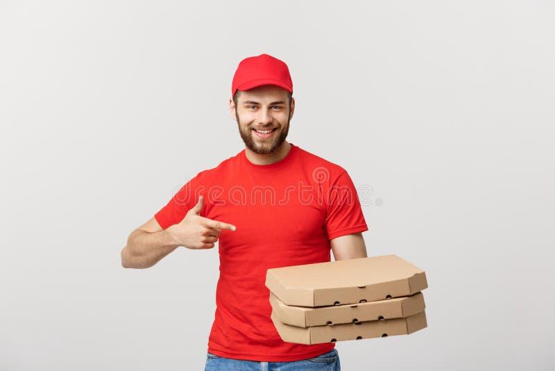 Doręczeniowy pojęcie: Przystojnej caucasian pizzy doręczeniowy mężczyzna wskazuje palec Odizolowywający nad popielatym tłem zdjęcie royalty free