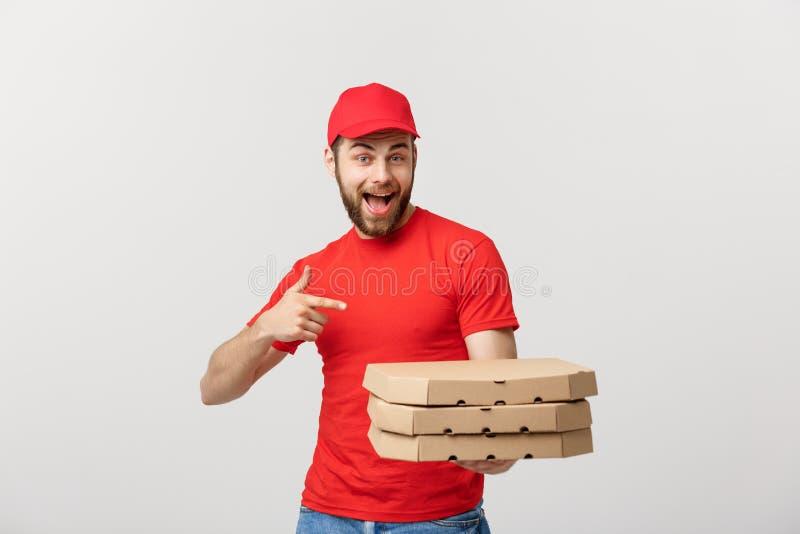 Doręczeniowy pojęcie: Przystojnej caucasian pizzy doręczeniowy mężczyzna wskazuje palec Odizolowywający nad popielatym tłem obrazy stock
