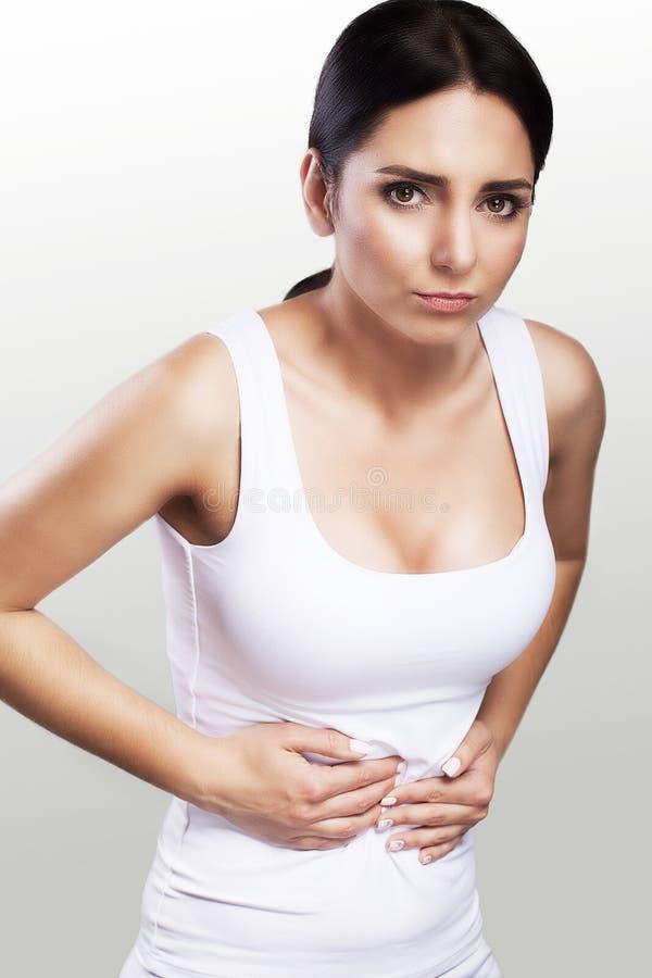 Dor abdominal fêmea Sensações dolorosas fortes menstruation gynecology cystitis Uma moça está guardando as mãos abaixo de seu sto imagem de stock