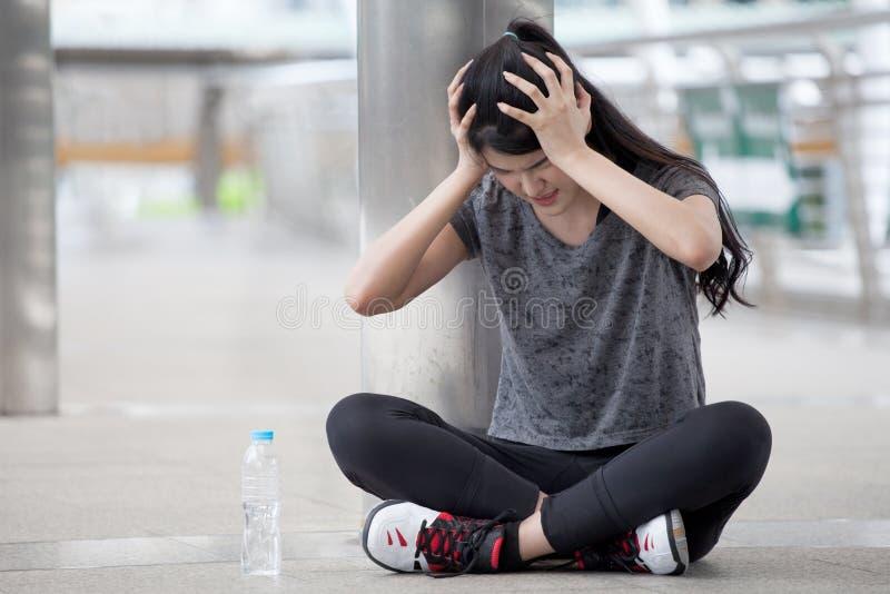 dor asiática da enxaqueca da dor de cabeça da jovem mulher da aptidão durante o exercício que exercita com uma garrafa de água na imagem de stock royalty free