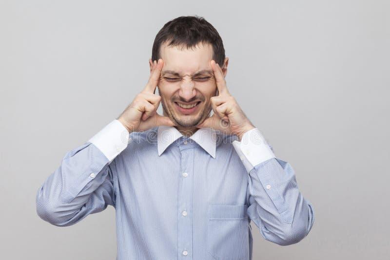Dor da dor de cabeça Retrato do homem de negócios irritado da cerda na posição azul clássica da camisa que guarda sua cabeça dolo fotografia de stock royalty free