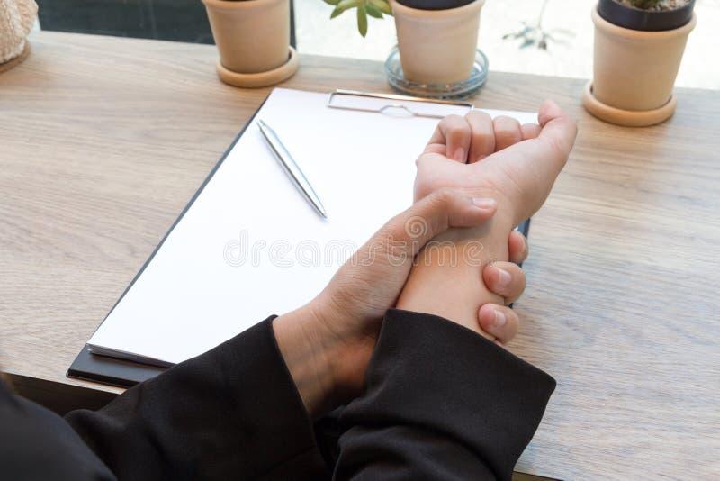 Dor da mão da mulher no conceito da síndrome do escritório da mesa fotografia de stock