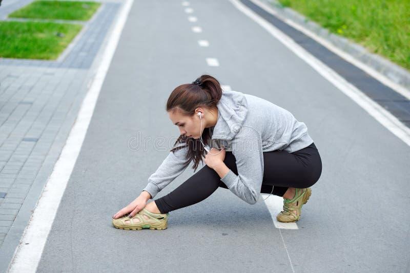 Dor da sensação da mulher do esporte com lesão de joelho na pista foto de stock royalty free