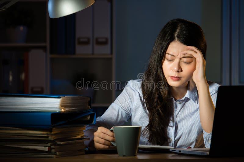 Dor de cabeça asiática do café da bebida da mulher de negócio que trabalha fora do tempo estipulado tarde foto de stock royalty free