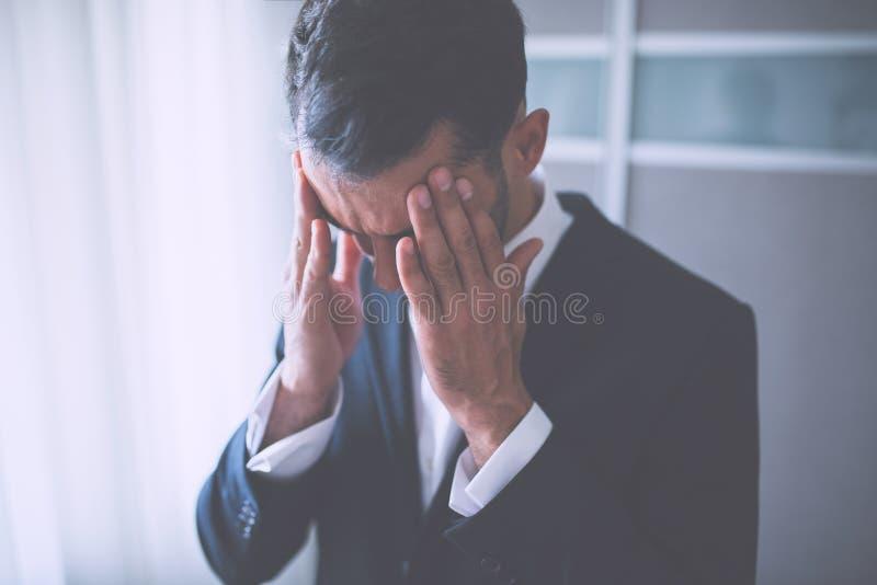 Dor de cabeça do homem de negócio Pensamento do problema no fundo do escritório fotos de stock royalty free