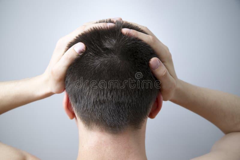 Dor de cabeça do homem no fundo cinzento imagens de stock royalty free