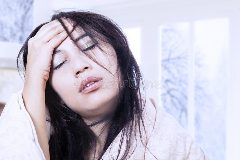 Dor de cabeça do martelamento com febre em casa imagem de stock