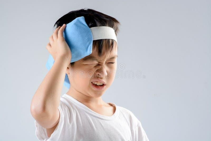 Dor de cabeça do menino e bloco do gel do gelo foto de stock