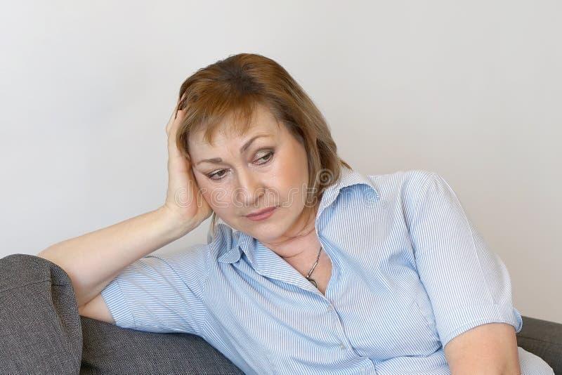 Dor de cabeça idosa da mulher A mulher espreme sua cabeça imagens de stock royalty free
