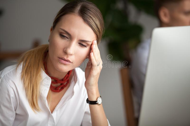 Dor de cabeça no conceito do trabalho, mulher de negócios nova forçada que sente s imagens de stock royalty free
