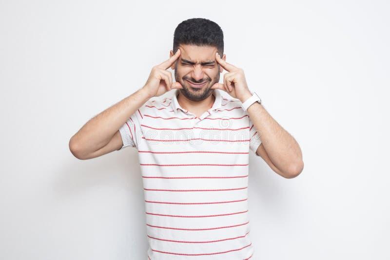 Dor de cabeça ou confution Retrato de homem novo farpado considerável confuso em posição listrada do t-shirt, guardando sua cabeç imagens de stock