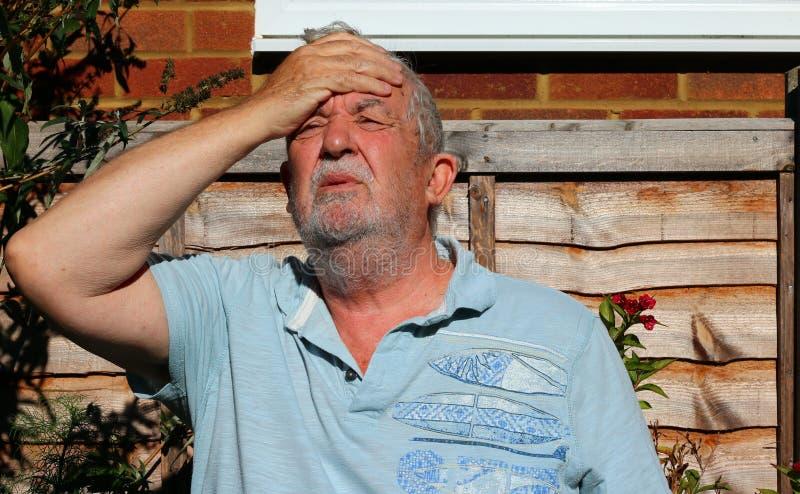 Dor de cabeça ou enxaqueca Homem que guarda sua cabeça na dor fotografia de stock