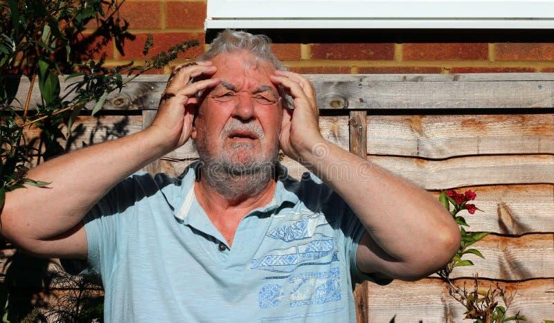 Dor de cabeça ou enxaqueca Homem que guarda sua cabeça na dor imagens de stock